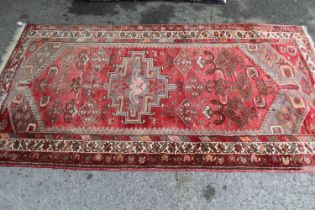 Hamadan rug of geometric design on wine ground, approximately 72ins x 40ins together with a small