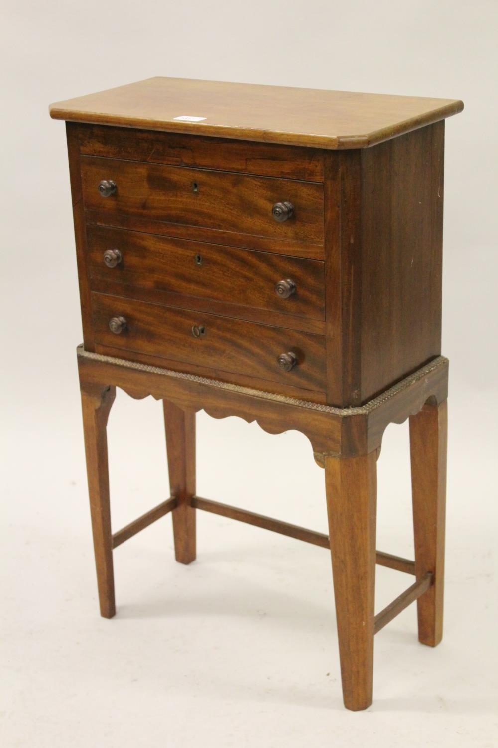 Small mahogany three drawer chest with knob handles on stand, 30.5ins x 19.5ins