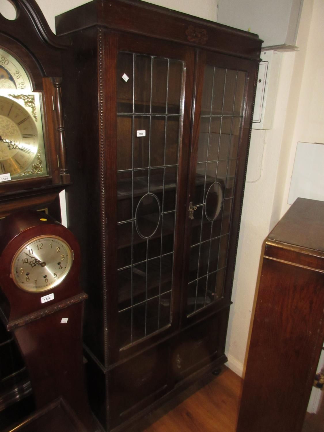 Mid 20th Century oak display cabinet having two leaded glazed doors with adjustable shelves above