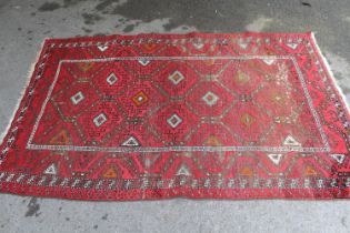 Afghan rug with a repeating hooked medallion design on a wine red ground with borders (some wear),
