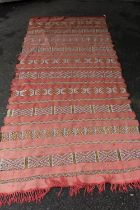 Sumak runner of geometric pattern on a red ground, 99ins x 44ins together with a similar smaller