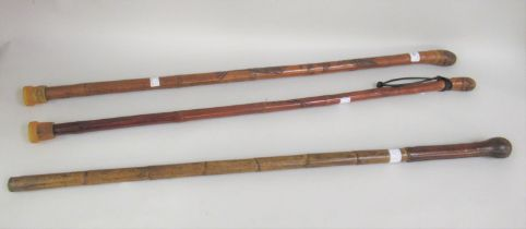 Two Japanese walking canes carved with various figures, together with another walking cane