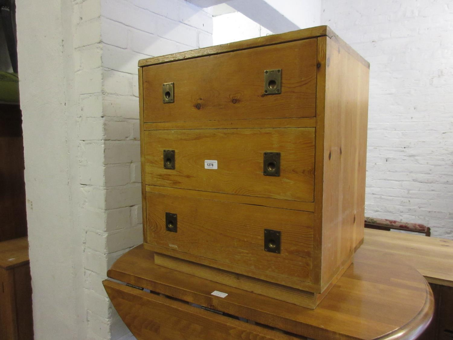 Stained pine three drawer bedside chest with brass inset military style handles