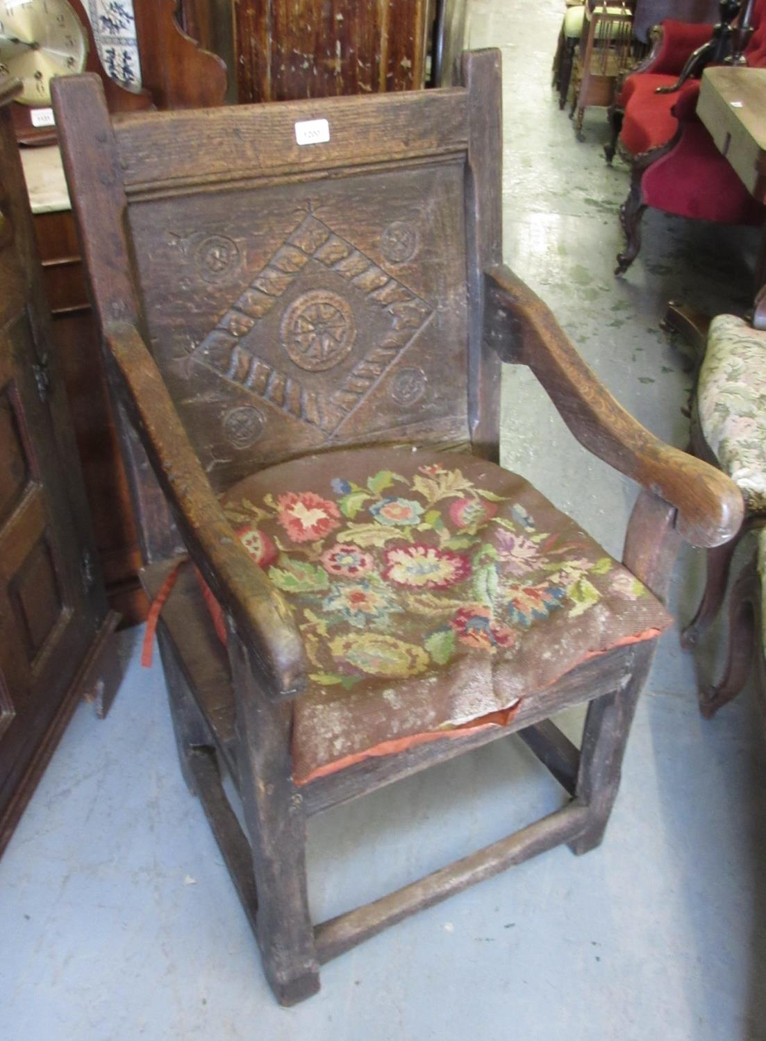 Antique oak Wainscot chair, the carved panel back and shaped arms above a plank seat, square cut
