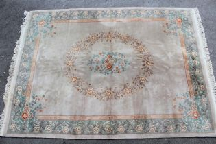 Chinese carpet with a central oval floral medallion on a beige ground with borders, 12ft x 9ft