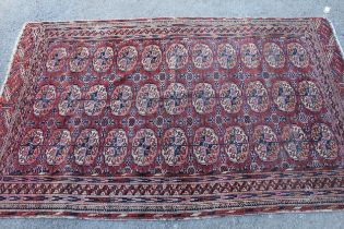 Small Turkoman rug with three rows of eleven gols, on a wine red ground with borders, 6ft x 3ft