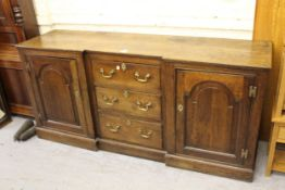 18th Century oak inverted breakfront dresser base, the three centre drawers with brass handles