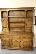 Good quality reproduction oak dresser, having moulded cornice above an arrangement of shelves and
