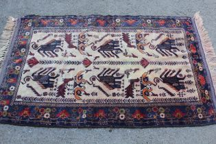 Small modern Belouch rug with animal and bird design on an ivory ground with borders, 4ft 10ins x
