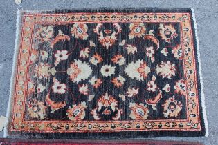 Small Afghan Ziegler mat with a floral design on a dark ground, 2ft 10ins x 2ft 2ins