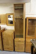 Modern Ercol light elm narrow side cabinet with a single glazed door enclosing wooden and glass