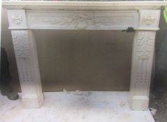 Large hand carved white marble fire surround having central leaf and foliate sprigs, supported by