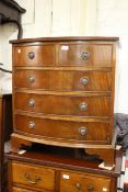 Small reproduction mahogany bow front chest of two short and three long drawers with ring handles