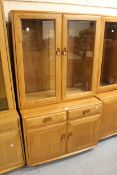 Modern Ercol light elm side cabinet with two bevelled glass doors enclosing shelves above two