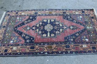 Kurdish rug with centre medallion and all-over floral design on a dark red ground with borders,