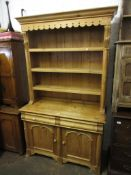 20th Century pine dresser having moulded cornice above three fixed shelves, with carved applied half