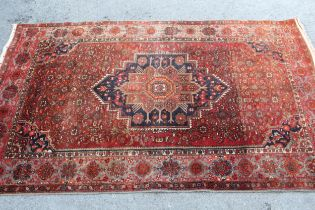 North East Persian rug with a single stepped medallion and all-over Herati design on a red ground