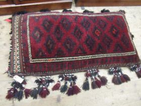Afghan carpet fragment covered floor cushion with bead and shell work tassels, 24ins x 44ins