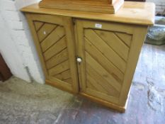 Victorian stripped pine two door cupboard of gothic design, on a plinth base, 31.5ins high x 35ins