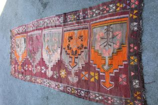 Kelim runner of all-over geometric design on a wine ground, approximately 10ft 6ins x 3ft 6ins
