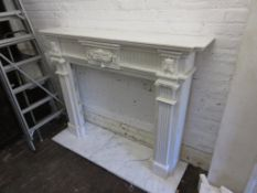 Large white marble fire surround having a moulded mantelpiece, above a central urn with bows and