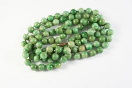 A SINGLE ROW UNIFORM JADE BEAD NECKLACE the jade beads measure approximately 9.7mm, 112cm long