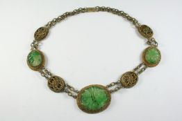 A CHINESE JADE NECKLACE formed with three oval-shaped pierced and foliate carved jade plaques and