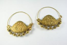 A PAIR OF EASTERN GOLD EARRINGS each with embossed Eastern inspired decoration, 9.5cm wide, 67