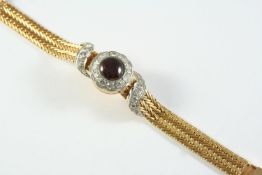 A LADY'S 18CT GOLD, GARNET AND DIAMOND WRISTWATCH BY BREITLING the signed circular dial with