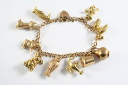 A GOLD CURB LINK CHARM BRACELET with padlock clasp and mounted with assorted gold charms, total