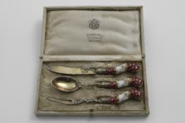 A LATE 19TH CENTURY GERMAN SILVERGILT-MOUNTED PORCELAIN CHRISTENING KNIFE, FORK & SPOON in a lined