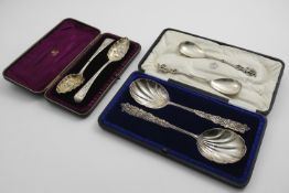 A LATE VICTORIAN CASED PAIR OF DECORATIVE, FRUIT SERVING SPOONS with fluted bowls, by Messrs.