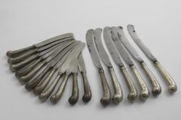 A SET OF SIX GEORGE II TABLE KNIVES with reeded pistol handles and steel scimitar blades with the