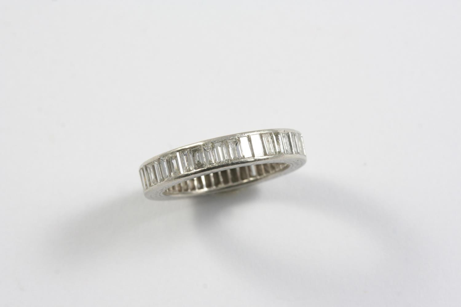 A DIAMOND FULL CIRCLE ETERNITY RING set with baguette-cut diamonds in platinum. Size M 1/2