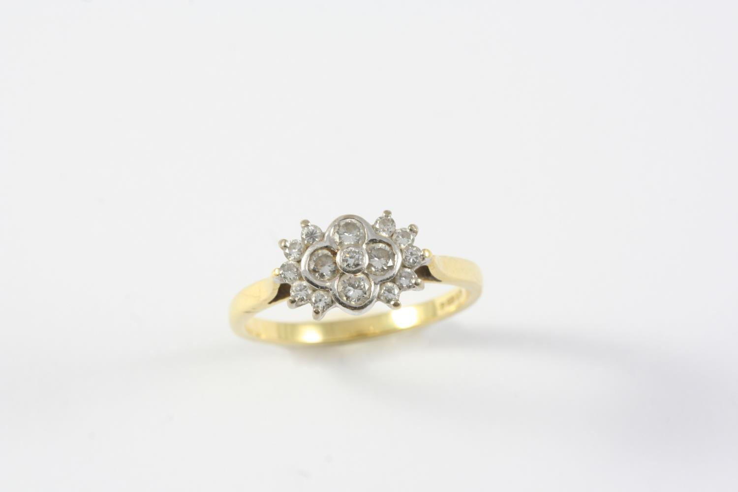 A DIAMOND CLUSTER RING mounted with graduated circular-cut diamonds, in 18ct gold. Size P 1/2