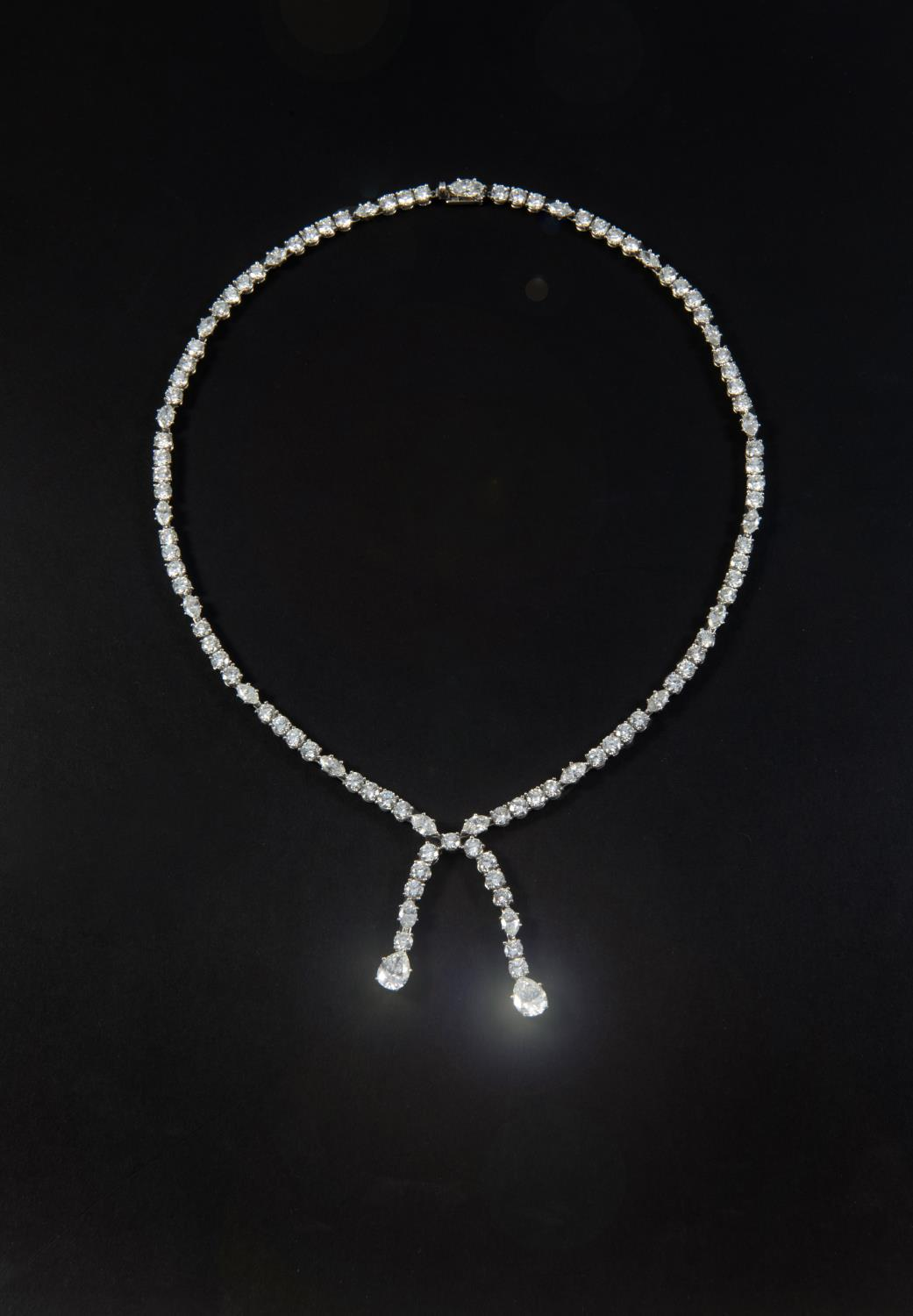 A DIAMOND DROP NECKLACE the necklace set with sections of four circular-cut diamonds, each divided