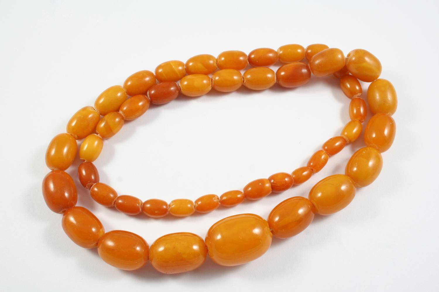 A GRADUATED AMBER BEAD NECKLACE 68cm long, 60 grams