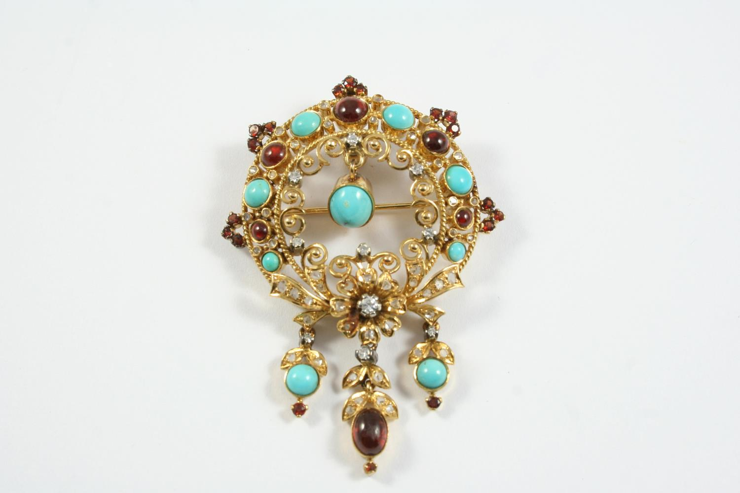 A GOLD, GARNET, TURQUOISE AND DIAMOND BROOCH PENDANT the 18ct gold openwork foliate mount is set