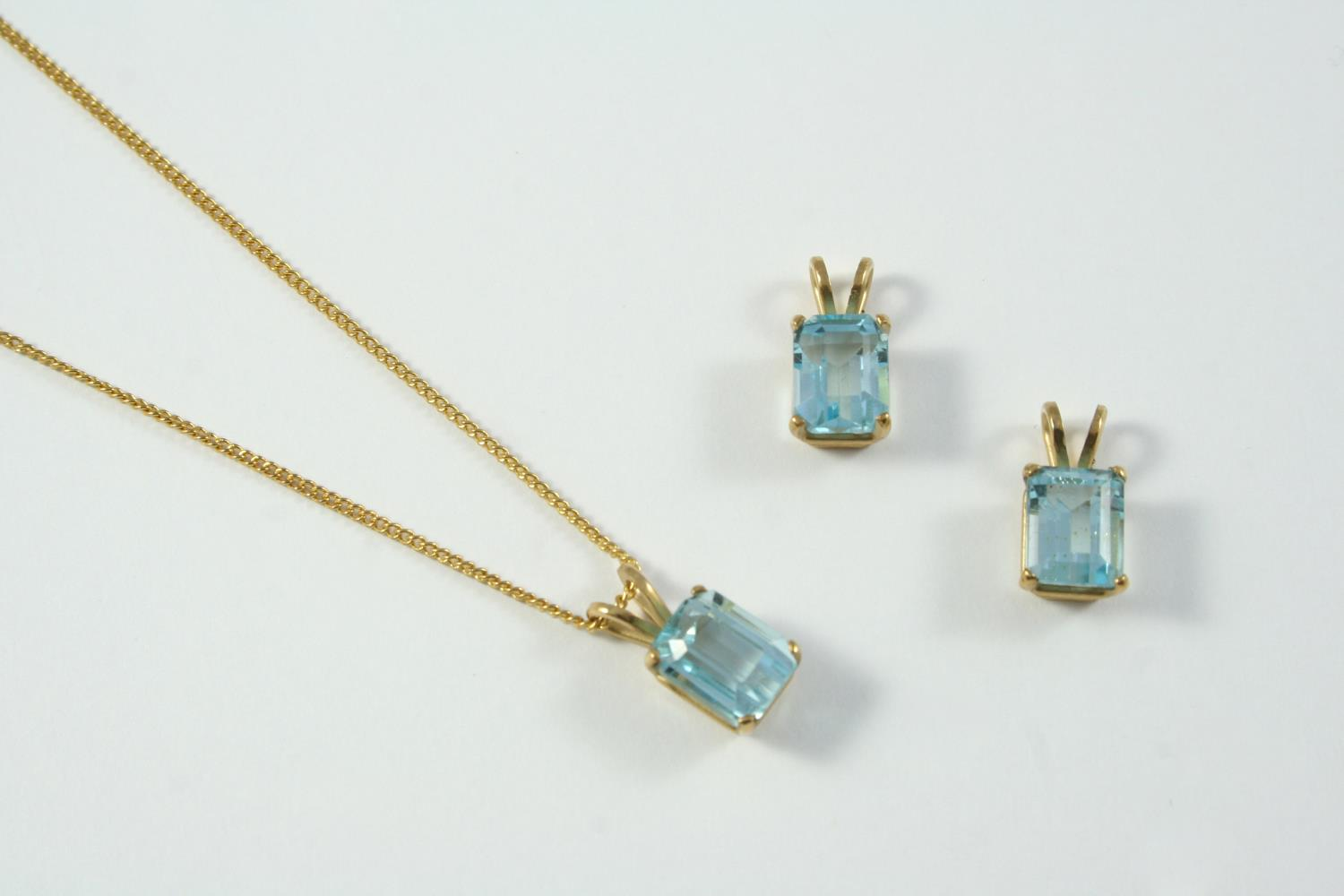 A SINGLE STONE BLUE TOPAZ PENDANT set with a step-cut blue topaz, in yellow gold, together with