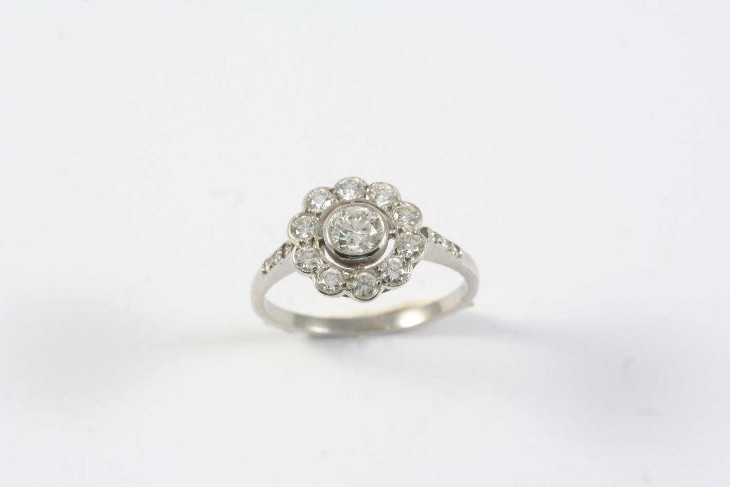A DIAMOND CLUSTER RING of flowerhead form, set with circular-cut diamonds, in platinum. Size M 1/2