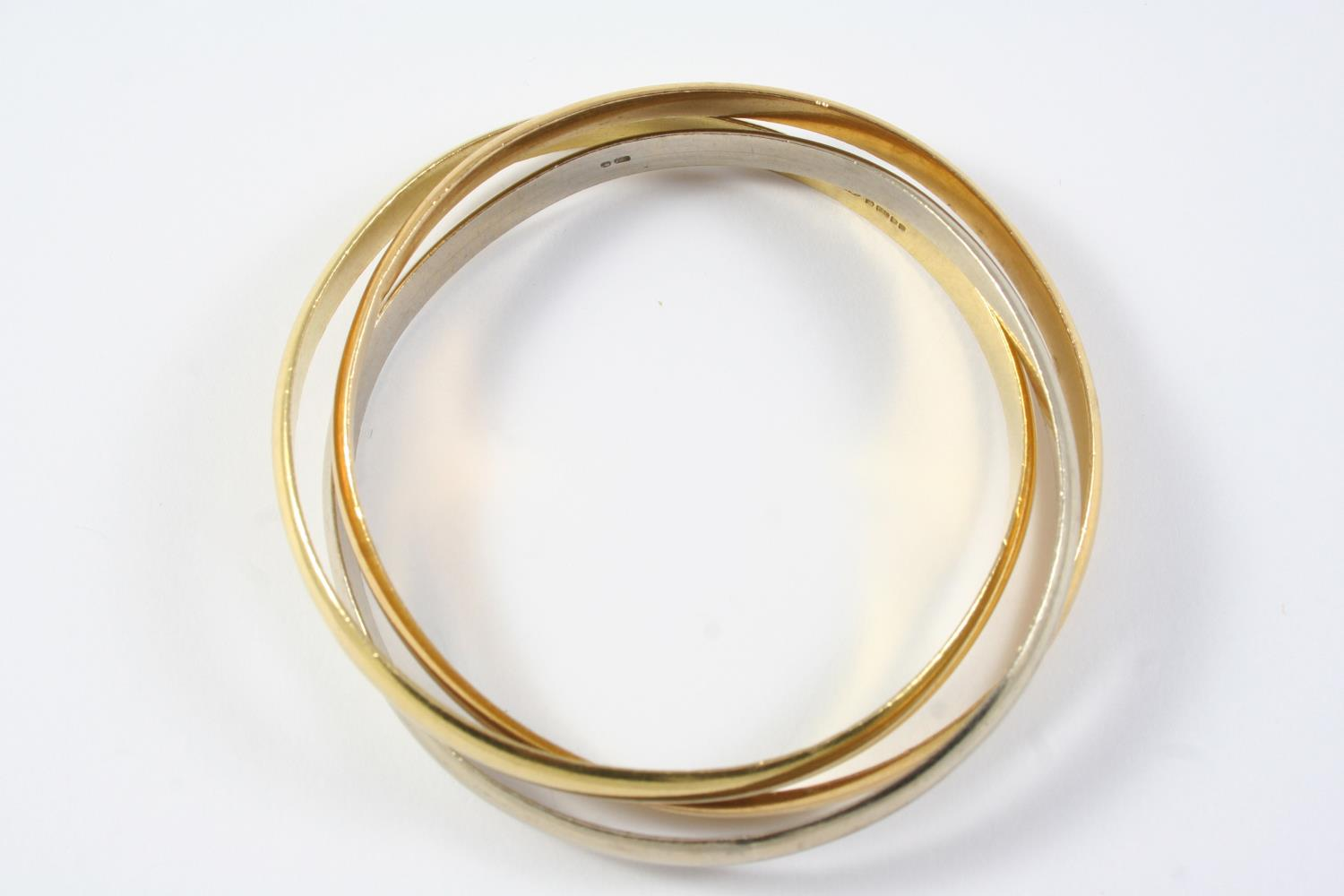 AN 18CT TWO COLOUR GOLD TRIPLE BAND BANGLE formed with three interlocking gold bands, two yellow