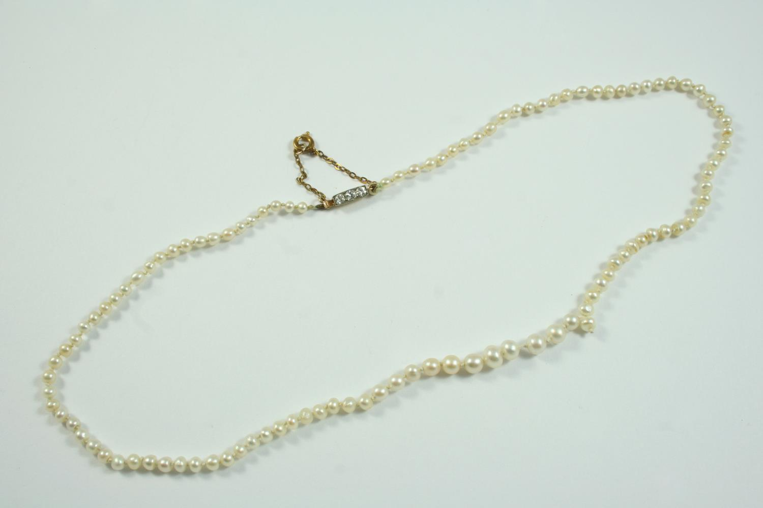 A SINGLE ROW GRADUATED NATURAL PEARL NECKLACE the pearls graduate to a rectangular-shaped clasp
