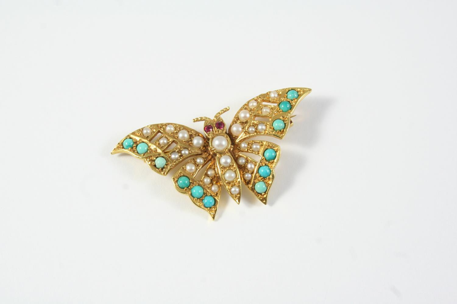 A TURQUOISE AND PEARL BUTTERFLY BROOCH formed with four graduated half pearls to the body, with