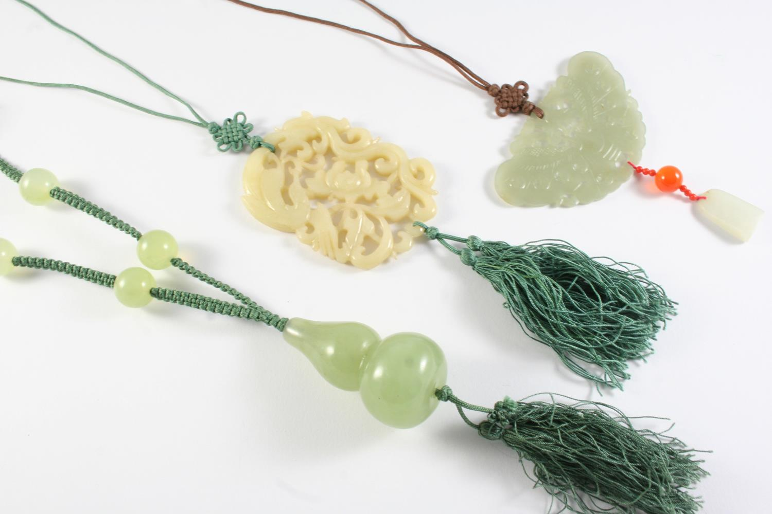 A CARVED JADE PENDANT of bird and foliate decoration, 6.5cm long, together with another carved