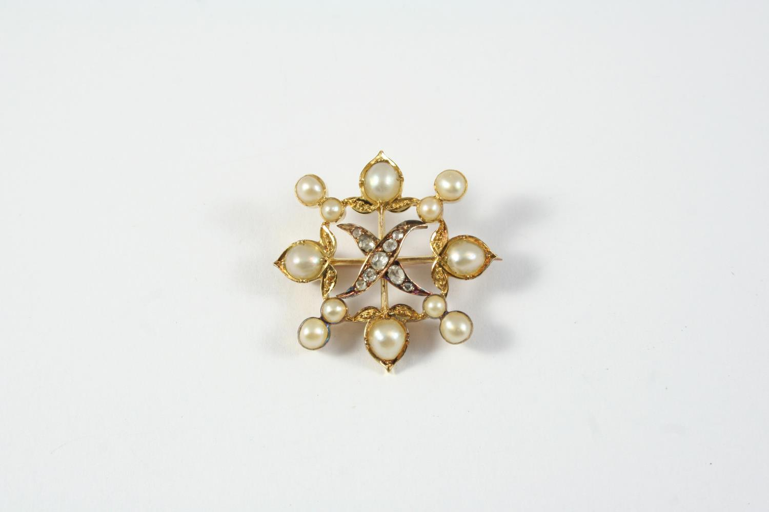 A DIAMOND AND PEARL QUATREFOIL BROOCH mounted with rose-cut diamonds and graduated half pearls, in