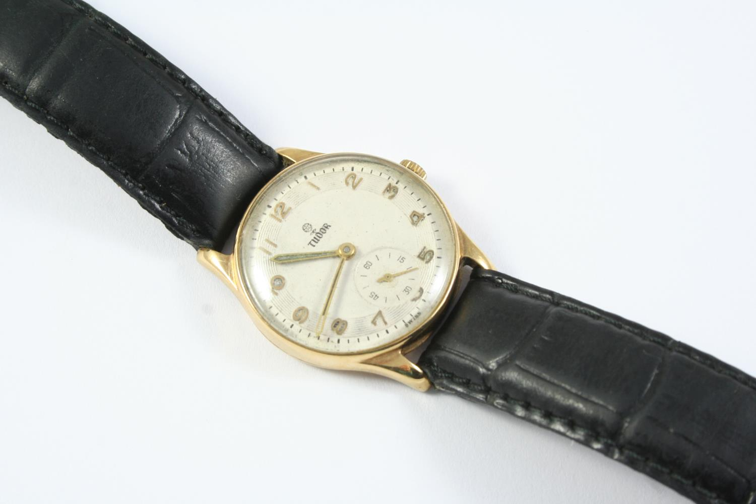 A 9CT GOLD MECHANICAL WRISTWATCH BY TUDOR the signed circular dial with Arabic numerals and