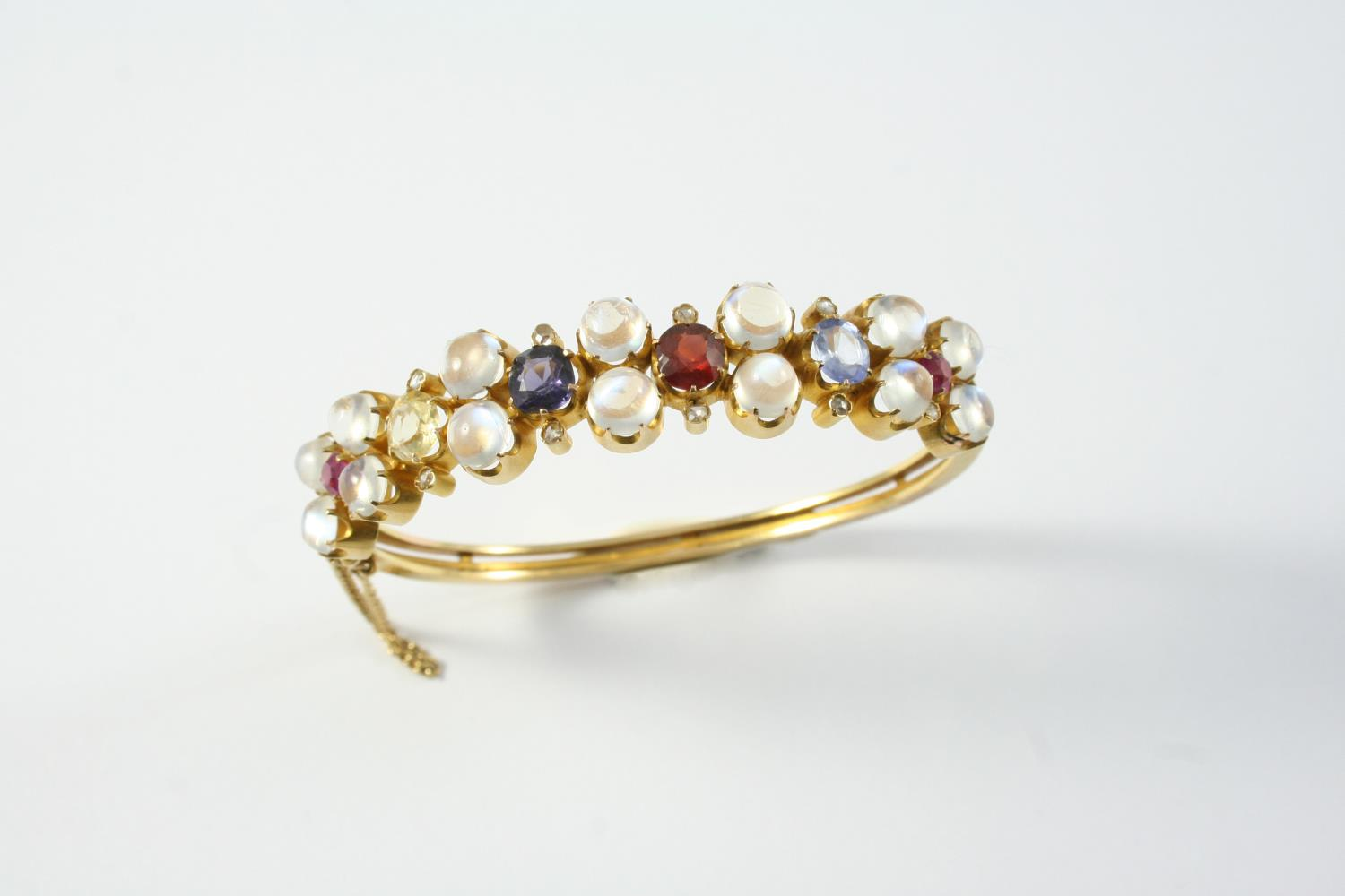 A GOLD, MOONSTONE, DIAMOND AND GEM SET HALF HINGED BANGLE mounted to one side with circular cabochon