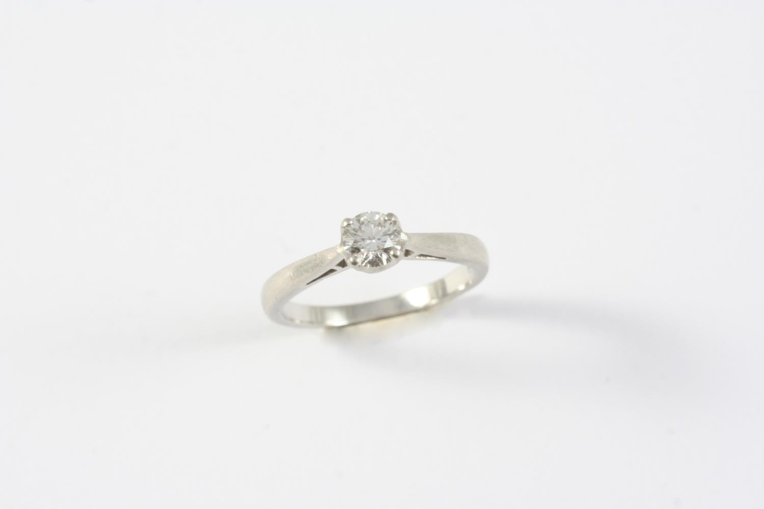 A DIAMOND SOLITAIRE RING the brilliant-cut diamond is claw set in platinum. Size J 1/2
