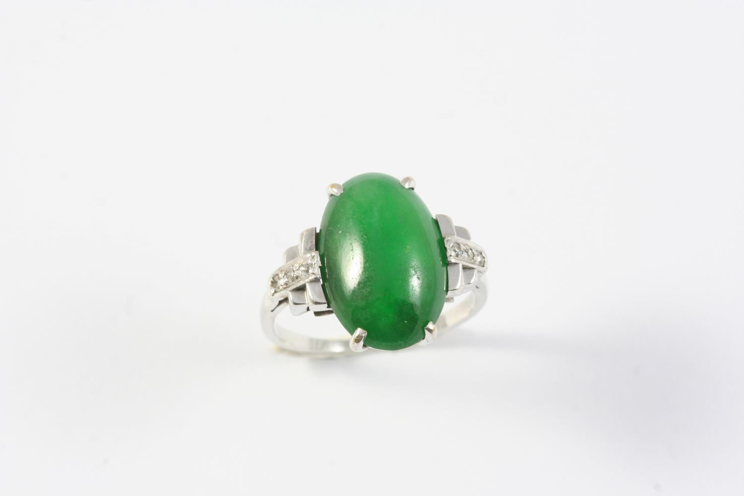 A JADE AND DIAMOND RING the oval-shaped cabochon jade is mounted with three circular-cut diamonds to