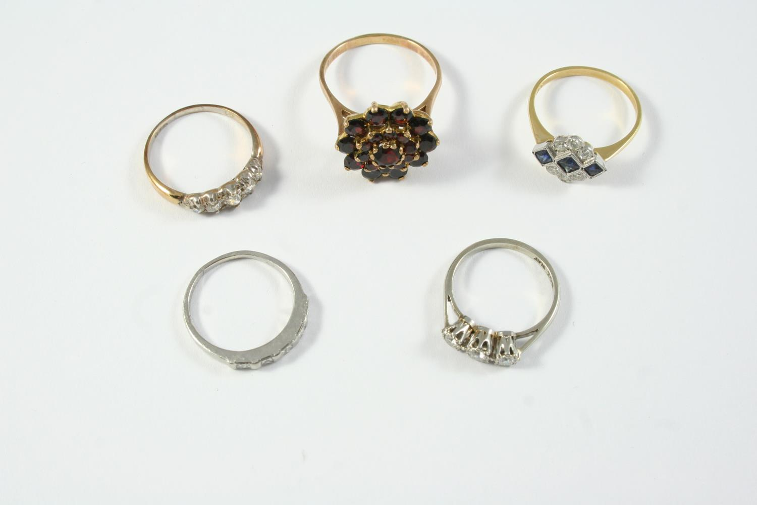 FIVE ASSORTED GOLD AND GEM SET RINGS including a diamond three stone ring, set in white gold and